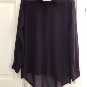Flot mørklilla transparent skjorte fra ICHI. Rummelig model, længere bagtil. 100% polyester. Køber betaler porto.