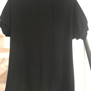 Flot sort top i glat stof med rib ved ærmerne og små slidser i siderne. Kan afhentes i Århus C. eller sendes for 37 kr. med Dao