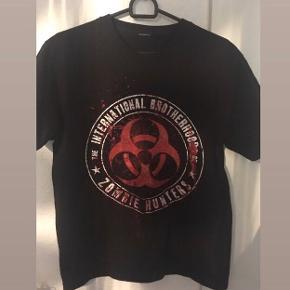 """#30dayssellout 🧟♂️🧟♀️ Så cool sort t-shirt med print/merchandise t-shirt med zombie design og quote: """"The international brotherhood of zombie hunters"""" (så er du totally ready til når en zombie apocalypse lige pludselig er i udbrud! 😂), købt på nettet, størrelsen har jeg klippet ud men mener det er en str M/38, unisex design. 💥  Kan passes af flere forskellige størrelser, alt afhængig af hvordan  man gerne vil have den skal sidde.  Sælges da den desværre er for stor til mig.  Aldrig brugt.  Købt til omkring 200-300 kr.  Hvis den skal sendes, betaler køber fragt.  Mvh Betina Thy"""