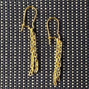 Fine, gyldne øreringe med små kæder.  Øreringene måler ca. 4,5 cm i længden.  Med lukkede, gyldne ørebøjler. Kan også fås lignende i sølvfarve og med øreclips.  Sælges for 55 kr. + evt. porto.  Kan afhentes på Frederiksberg.