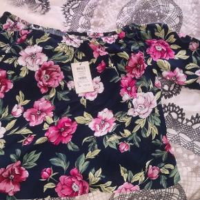 Helt ny off should bluse i blomstret mønster, perfekt til sommer eller forår. Jeg købte den i håb om at jeg kunne passe den, men det kunne jeg desværre ikke. Det er synd den bare ligger i mit skab så derfor søger den en ny ejer.
