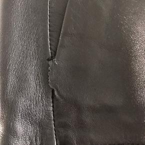 Læder med polyester ligning. Lille slip i syning ved lomme
