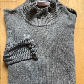 Sød lysegrå bluse fra Kaffe. Blusen er med turtleneck og har lidt detalje ved ærmerne.