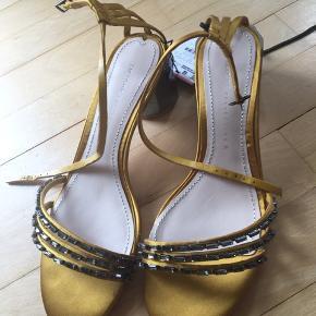 Skøn og meget feminin sandal med lille hæl. Farven ligger mellem solgul og karrygul.  Nypris 575