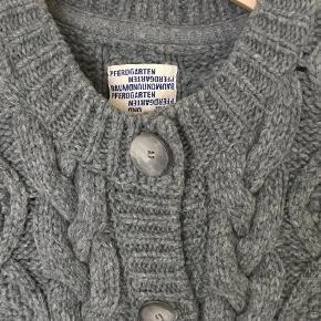 """Varetype: Lang Farve: Grå Oprindelig købspris: 3200 kr.  Super lækker kabekstrik strikjakke/cardigan i 100% uld Stand skrevet som """"god, men brugt"""", men den er tæt på """"nærmest som ny"""". Se også mine mange andre skønne ting til salg :-)"""