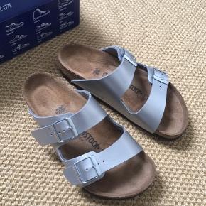 Helt nye Birkenstock sandaler i sølvfarvet glat skind. Har været prøvet på og gået med højst en halv time indendørs.  De er str 36 og bred i faconen. Sælger fordi de er for brede til min fod.  Sælger desuden rigtigt meget andet - både sko og tøj fra bl.a. Custommade, rabens saloner, day, acne, lollys laundry, project aj 117 m.m. ..