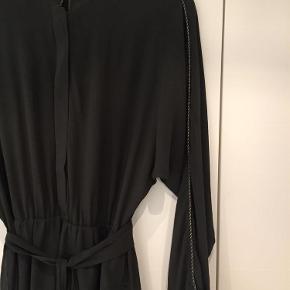 Varetype: Kjole Farve: Armygrøn  Smuk silkekjole fra Gestuz. 100% Silke. Lining 100% Viscose.  Længde målt fra skulder er ca. 123 cm.  Brugt en gang.  Tynde snore til at holde bæltet er gået løs, men kan uden problemer syes.