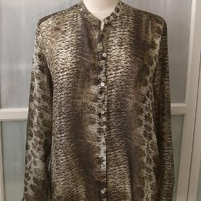 Bytter ikke! Min mp. kr. 875,-. Plus pakkeporto kr. 38,- uden omdeling, forsikret. DAO. Købspris kr. 1.600,-.   Super smuk skjorte, fra Sand, str. 42. Farve: brune men har et skær af vissengrøn, og cremet toner fra lys til mørkere. 100% Silke. Silken er naturlig letvægtsfiber med en glansfuld overflade. Skjorten er gennemknappet. Længere bagpå. Størrelsesguide str. 42: Bryst mål 102 cm Talje mål 84 cm Hofte mål 110 cm Længde fra nakken og ned 70 cm For og bag stykket målt ved bryst linjen, 112 cm. For og bag stykket målt ved hofte linjen 116 cm Kommer fra et ikke ryger hjem. Hænger i dragtpose.