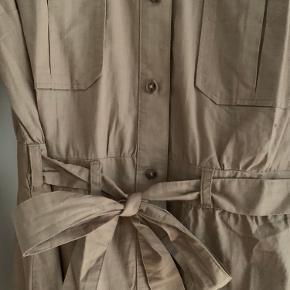 Fin sandfarvet/beige kjole fra HM Divided, med lommer og bindebånd i taljen. Aldrig brugt.
