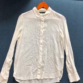 Skjorte i 100% mulberry silke, med gyldne metal detaljer på flipperne. ( De har mistet lidt farve efter vask) Skjult knaplukning med perlemors knapper.  Mål taget ustrakt: Bryst og Talje 49x2cm Ærmegab 22cm Ærmelængde fra armhulen og ned 46cm Skuldersøm til Skuldersøm 39cm Længde fra skulder og ned foran 65cm, 2 cm længere bagpå  Bytter ikke så lad venligst være med at spørge