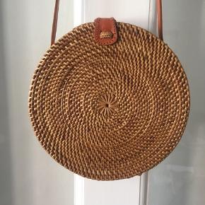 Meget fin taske i rattan/flet med læderstrop og lukning. Aldrig brugt. Købt i Grækenland for 100€. Intet mærke. Strop: 115 cm Taske diameter: 20 cm Taske dybde: 7 cm