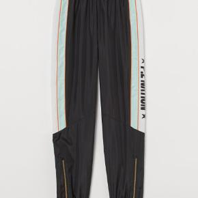 P.E NATION x H&M.  Træningsbukserne er i hurtigtørrende funktionsmateriale. Bukserne har høj talje med bred elastik og vide ben, som er lidt smallere forneden. Elastik og synlig lynlås forneden på benene. Foret med mesh. Polyesteren i buksernes yderste lag er genvundet.