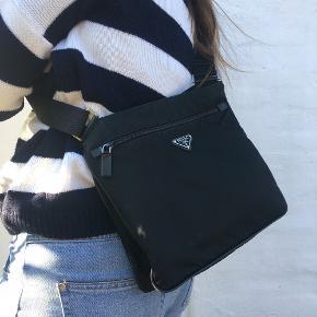 PRADA NYLON CROSSBODY BAG  Farve: sort  Materiale: Nylon Taske mål: 30 x 26 cm Skulderrem: 32 - 60 cm  Ingen: boks, kvit, pose eller andet. Kun tasken