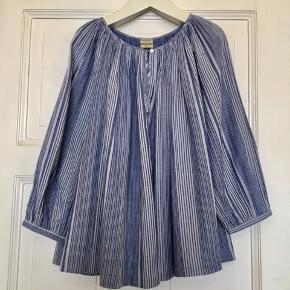 Fin pilotto bluse fra By Malene Birger i 100% bomuld. Kun brugt et par gange og i flot stand uden hullet, pletter, fnuller eller lign. En stor str. 34, da den er oversize i modellen. Brystmål: 67 cm fra armhule til armhule, dvs 154 cm i omkreds. Længde: 60 cm fra nakken og ned. Søgeord: lyseblå skjorte bluse tunika stribet shirt blå striber