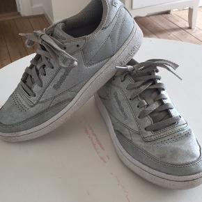 Reebok Classic Club C 85 sko i sølv. Skoene er i god stand, men trænger dog til at blive vasket/renset. Skoene er str. 37,5, men er store i størrelsen og svarer til en str. 38.