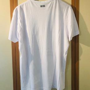 Hvid T-shirt fra Hugo Boss med stor styk for samt lille tryk omme i nakken sælges pga pladsmangel. T-shirtsen fremstår som ny da den nærmest ikke har vært brugt siden den blev købt i magasin i Århus.  Kom med et fair bud