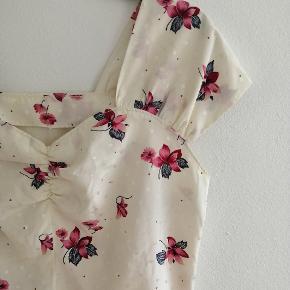 Smuk vintage top med blomster og blade i satin agtigt stof. Flotte detaljer ved bryst og ærmer.