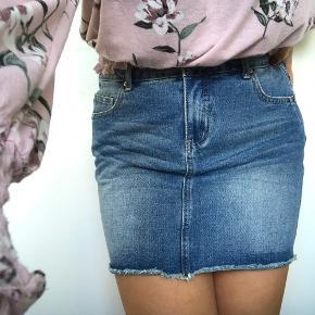 Lavtaljet denim nederdel med lommer bagpå i størrelsen L/XL  (Fragt er ikke inkluderet)