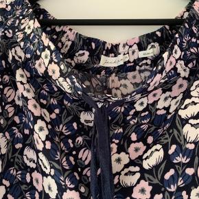 Florlette bukser fra Jackpot med mørkeblå baggrund og blomster i hvid/pudder/rosa. Bindebånd i livet og små lommer.