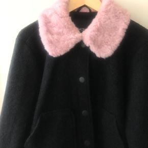 """Efterårs jakke i sort med to lommer og en lyserød """"fake pels krave"""". Byd."""