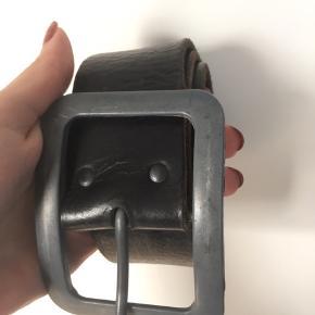 Bredt bælte i slidt sort læder/fake læder (ikke sikker på materialet). Gives væk