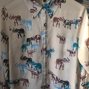Toplækker skjorte i det fedeste, silkeagtige stof med lidt strech i. Creme/beige bundfarve med elefanter på. Skøn at have på - sælges udelukkende, fordi den er lidt for stor til mig. Brugt ganske få gange