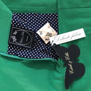 Skøn Edith & Ella nederdel i fed grøn farve og med prikket for og fine detaljer på bælte og knapper. Rigtig god pasform, der er lidt stræk i stoffet. Aldrig brugt, stadig med prismærke.