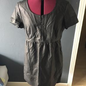Kjole i imiteret læder med lommer.