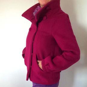 Ulden jakke fra H&M i flot, cerise / pink farve, der lyser dejligt op her i de mørke måneder.  Har ikke været brugt og jakken fremstår som helt ny.  Knappes med matchende trykknapper nederst og store, stofbetrukne knapper øverst.  Str. 40.  Sælges for 175 kr. + evt. porto.  Kan afhentes på Frederiksberg.