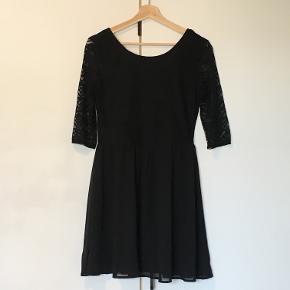Kjole med zig-zag blonde i overdelen og chiffonlignende materiale på underdelen. Kjolen er med 3/4 lange ærmer og har en dybere ryg udskæring og en forholdvis høj halsudskæring. Kjolen er en str. 42, men er dog lille i størrelsen, og svare normalt til en str. 38-40 men har stræk i sig. På sidste billede kan I se kjolen på.  Kjolen er helt ny, og har stadigvæk prismærke på! Kjolen blev købt i anledningen af min fødselsdag tilbage i 2015, dog blev festen aldrig til noget, og kjolen blev derfor aldrig brugt.  Hvis du ønsker flere spørgsmål eller anden information om kjolen så endelig skriv.