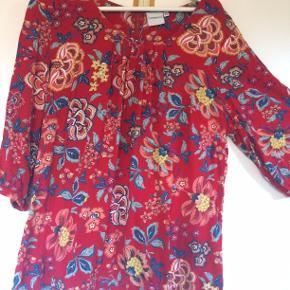Flot rød bluse med elastik forneden, den er kun brugt få gange medn har en anelse fnuller på maven. bm 65 x 2 og læ 67 cm.