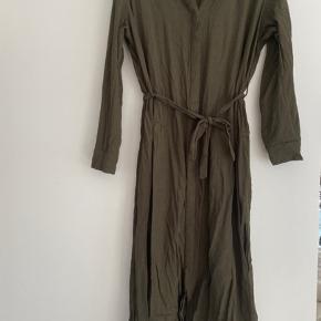 Fin kjole fra Envii i en dyb grøn/oliven farve. Kjolen er i en god kraftig kvalitet, så den er ikke gennemsigtig. Har knapper og bindebånd.   Afhentes i Århus c eller sendes med DAO.