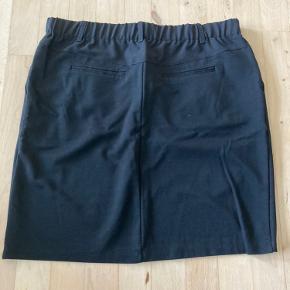 Klassisk, sort nederdel med elastik. Kan både sættes i taljen eller ved hofterne.