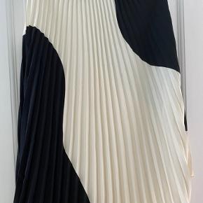 Plisseret, asymmetrisk nederdel fra H&M Trend i råhvid og mørkeblå (næsten sort). Str. 34, men passer også en lille 36. Enkelte brugsspor.