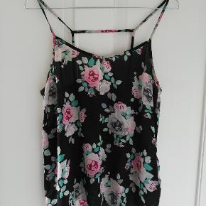 Sød top med blomster og fin strop-detalje bagpå. Uden mærke, svarer til en størrelse S.  Tager ikke billede af tøjet på. 🌺