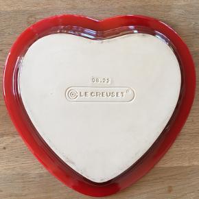 Hjerteformet Le Creuset fad. Rød yderside, beige/sand inderside. Ingen skader. Smukt på julebordet bl.a. til nødder, konfekt eller en smuk juledekoration.  En flot værtindegave fx. Nypris +/- 370kr