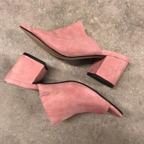 Mules i ruskind. Aldrig brugt, men lider desværre af skader/mærke efter at have lagt i en kasse med sorte sko.