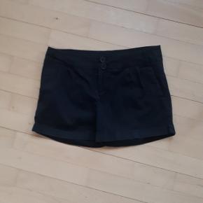Sorte shorts fra Vila i str M.  Måler ca 77 cm i talje omkreds.   Den nederste knap foran sidder meget løst, og trænger til at blive syet bedre fast.  Kan hentes i Roskilde eller sender mod betaling af fragt.  #30dayssellout