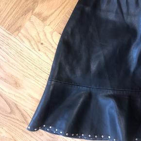 Super fin nederdel fra Zara i imiteret/PU læder med detalje i bunden af skørtet. Brugt, men ikke noget der kan ses. Køber betaler fragt.
