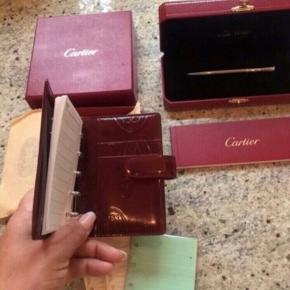 Fineste kalender i bordeaux præget skind fra Cartier  Kommer i original æske og så fin  Kun været samlet med tilbehør og ligget på kontoret, er fin og som ny.  Lidt nyt notes tilbehør medfølger.  Kuglepen sælges seperat