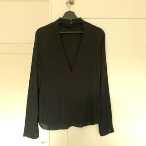 Sælger denne fine bluse med høj hals og åben ryg fra Envii.