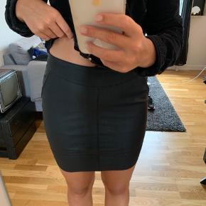 Læderlook nederdel med lynlås bagpå og lommer i begge sider