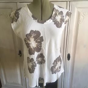 Rigtig flot hvid bluse med store nougat farvet blomster. Viskose med let skinnende overflade. BM 60 x 2 - L 70 cm. Sender gerne.