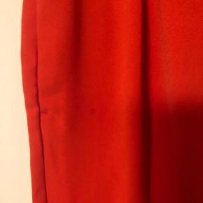 Røde bukser. Lidt store i størrelsen. Har en lille plet på højre side, men ikke noget man lægger mærke til.