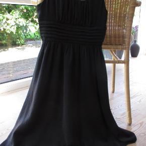 Rigtig sød elegant sort kjole fra H&mKjolen er i 2 lag og har i hver side 4 tynde stropper.Har elasik bag på, hvilket gør den fleksibel og behagelig at have på.I let skinnende stof, der gør den elegant, at se på.  Hel længde ca. 83 cm  Sendes som forsikret pakke med DAO/Coolrunner, hvis ikke andet aftales