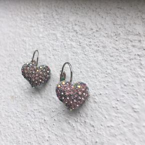 Smukke sølv øreringe med hjerter som har fine små sten i rosa og sølv nuancer.