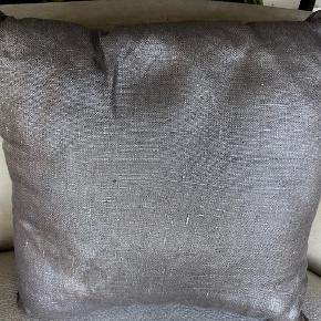 Skøn og virkelig smuk pude i linnen fra Zenza. Puden er håndlavet i Egypten. Den er changerende i sølv med et svagt raffineret rosa skær. (Svært at fange på billederne).  Mærke: Zenza Størrelse: Ca 35 x 35 cm Grundfarve: Sølvchangerende med svag rosa tone  Zenza kombinerer ofte gamle teknikker med et moderne twist i deres design og udvikler en meget elegant, intim men alligevel moderne atmosfære.  Nypris: 45 EUR = ca. 330 kr  Købt i Holland. Ca. 2 år gammel. Bare ligget som pyntepude. Fremstår rigtig flot.