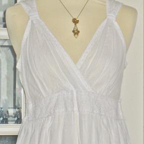 """100 % NY kjole med tag.  Flot hvid bomuldskjole med blonde under brystet og blomster-broderi på nederdelen i hvid i hvid. Nederdelen er i 2 lag, så den er ikke gennemsigtig. Ryggen af kjolen er med elastik, så målene er flexible.  Størrelsen hedder """"One Size"""", men se målene nedenfor.  Brystvidde: 48-55 cm x 2 pga elastik-ryggen Livvidde: 40-50 cm x 2 pga elastik i ryggen Længde: 103 cm ...   Ingen byt og prisen er fast"""