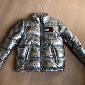 Sølv jakke fra Tommy Hilfiger.  Har slid på sølv efter rygsæk, derfor den lave pris, ellers i god stand.  Kvittering haves. Bud modtages 😊