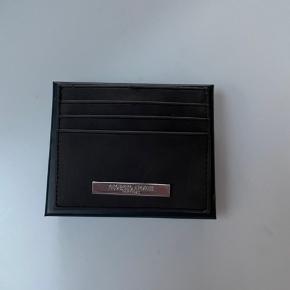 Giorgio Armani kortholder i brunlig sort farve. Pungen er brugt få gange, og har derfor INGEN tegn på store skader.  Stil gerne spørgsmål eller bud i chat.  Fået i gave
